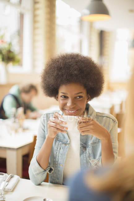 Happy young women drinking coffee in cafe — Stock Photo