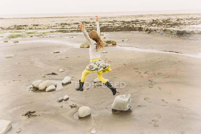 Exuberant girl jumping for joy on beach rocks — Stock Photo