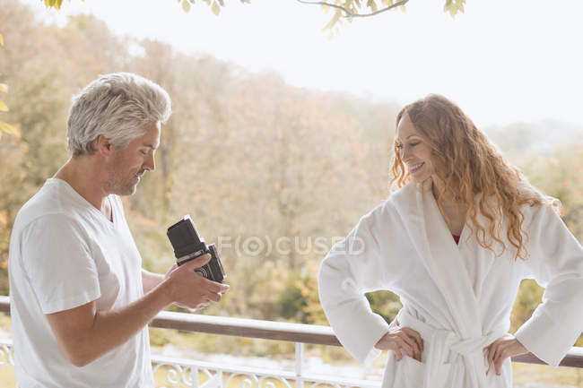 Man with old-fashioned camera photographing woman in bathrobe on autumn balcony — Stock Photo
