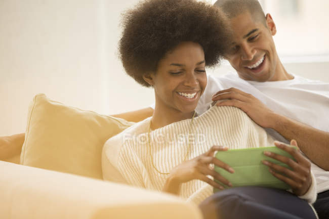 Couple using digital tablet on sofa at home — Stock Photo