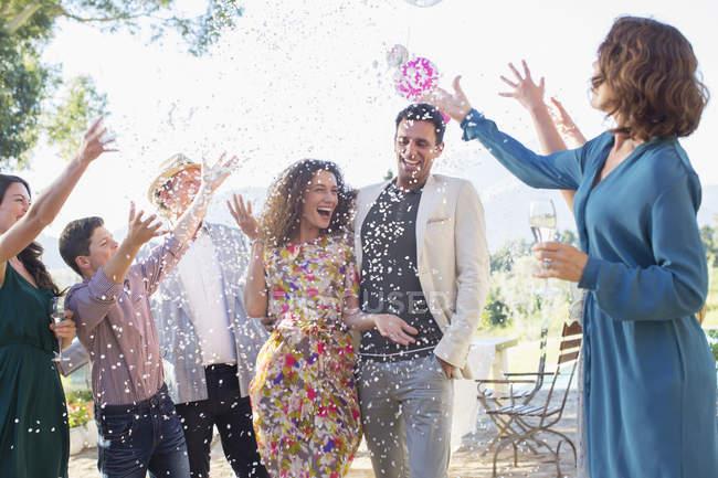 Familia lanzando confeti en pareja recién casada - foto de stock