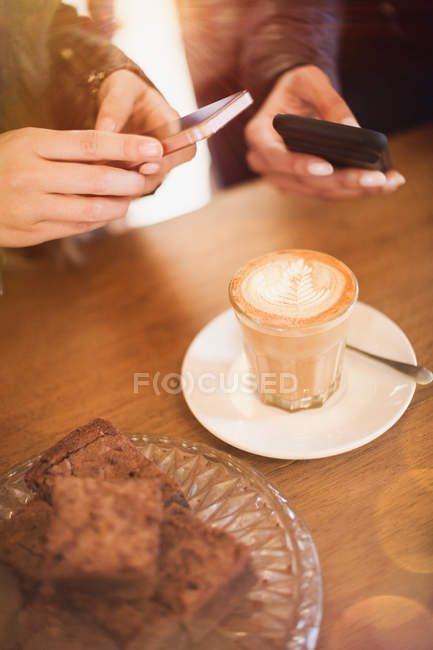 Жінки з камери телефонів фотографування капучино дизайн в кафе таблиці — стокове фото