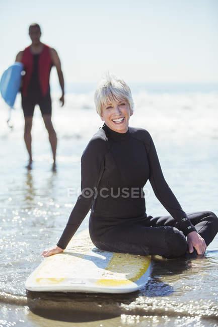 Retrato de mulher idosa na prancha de surf na praia — Fotografia de Stock
