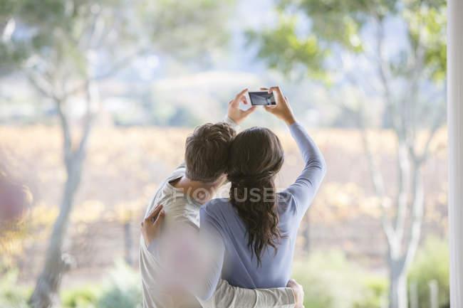 Pareja tomando selfie con teléfono de la cámara en el patio - foto de stock