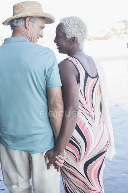 Seniorenpaar hält Händchen und geht am Strand spazieren — Stockfoto