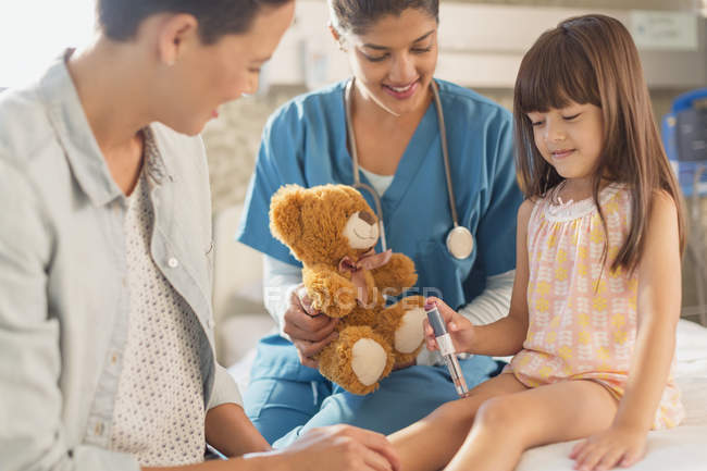 Female nurse with teddy bear watching girl patient using insulin pen in hospital room — Stock Photo