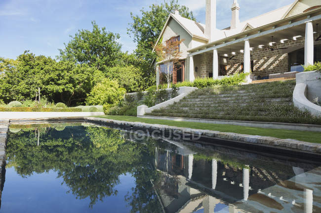 Piscina contra casa moderna de lujo - foto de stock