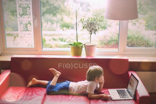 Ragazzo che utilizza laptop su divano in pelle rossa in soggiorno — Foto stock