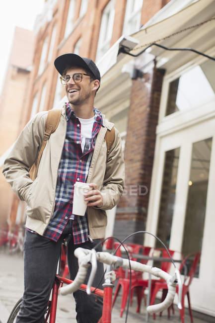 Человек пьет кофе на велосипеде на городской улице — стоковое фото