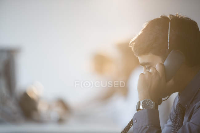 Businessman talking on telephone in office — Stock Photo