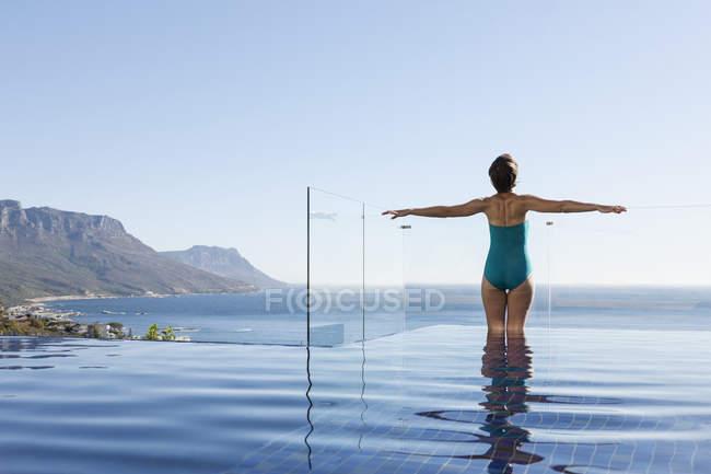 Женщина купается в бассейне с видом на океан — стоковое фото