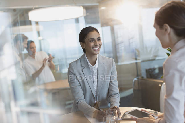 Smiling businesswomen talking, using digital tablet in conference room meeting — Stock Photo
