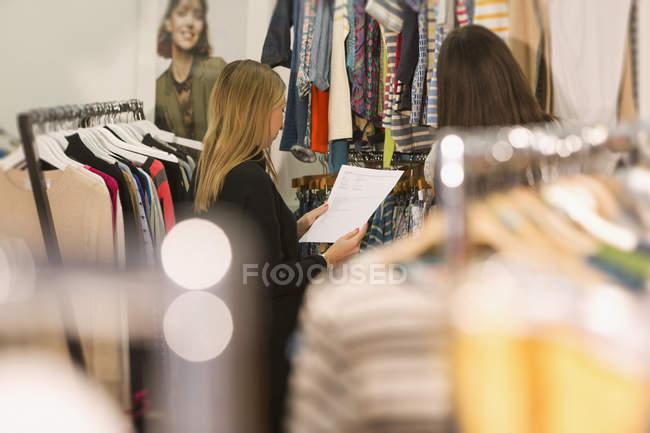 Мода покупців вивчення одяг на стелажах — стокове фото