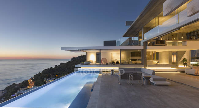 Illuminated modern, luxury home showcase exterior patio with lap pool and ocean view at twilight — Stock Photo