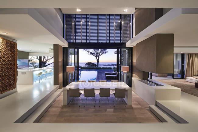 Interior del escaparate de la casa de lujo moderno con vista al mar al atardecer - foto de stock