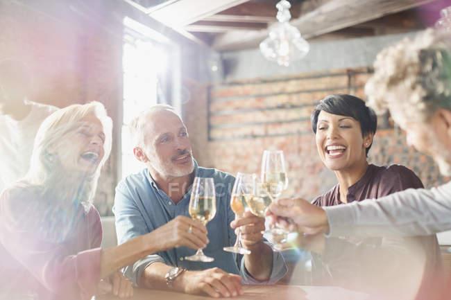 Amigos brindando com taças de vinho brancas na mesa do restaurante — Fotografia de Stock