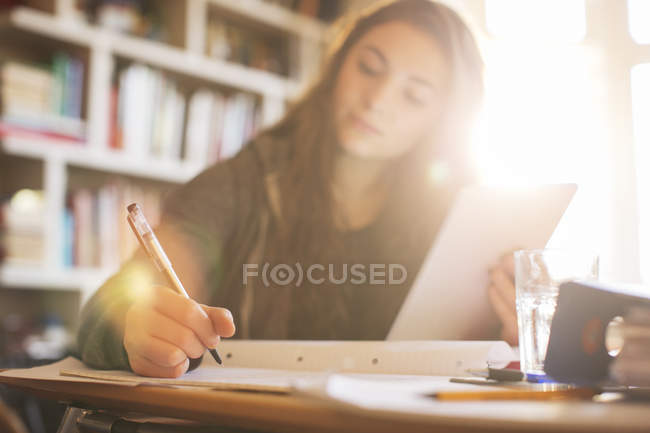 Teenage girl with digital tablet doing homework at sunny desk — Stock Photo