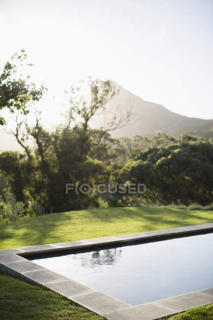 Sun shining over mountain and luxury lap pool — Stock Photo