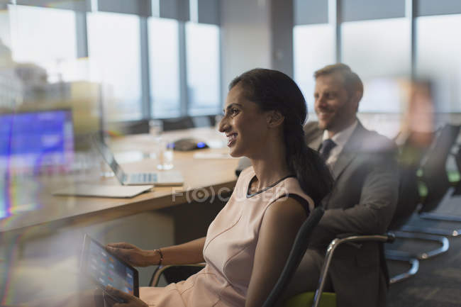 Smiling businesswoman with digital tablet in conference room meeting — Stock Photo