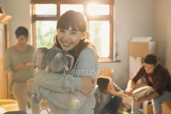 Portrait smiling young woman hugging stuffed elephant — Stock Photo