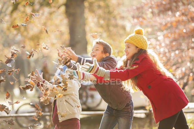 Boys and girl catching autumn leaves — Stock Photo