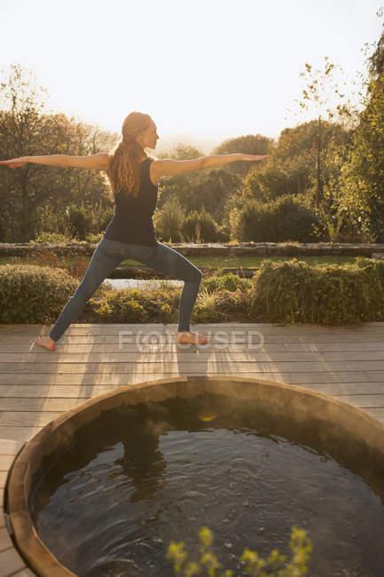 Donna che pratica yoga guerriero 2 posa sul patio autunno con vasca idromassaggio — Foto stock