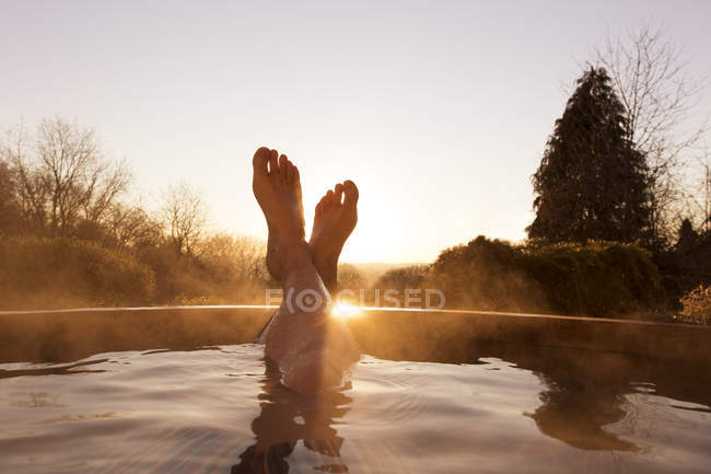 Man feet raised out of pool — Stock Photo