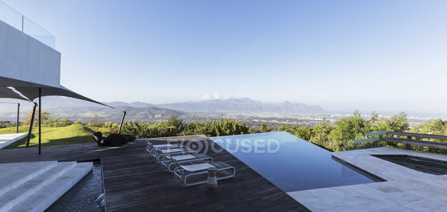 Modern luxury home showcase exterior with infinity pool and mountain view under blue sky — Stock Photo