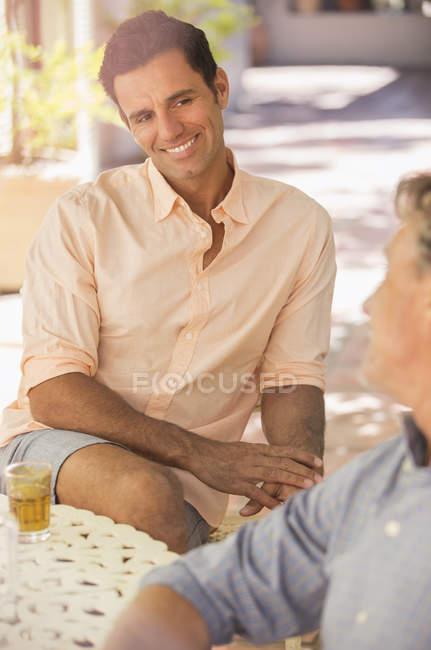 Батько і син сидів за столом, насолоджуючись на відкритому повітрі — стокове фото