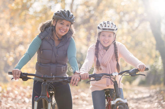 Portrait of smiling mother and daughter on mountain bikes in woods — Stock Photo