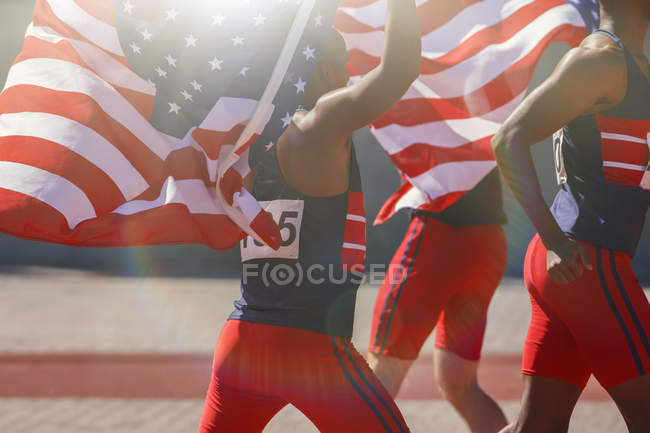 Легкоатлеты держат американские флаги на треке — стоковое фото