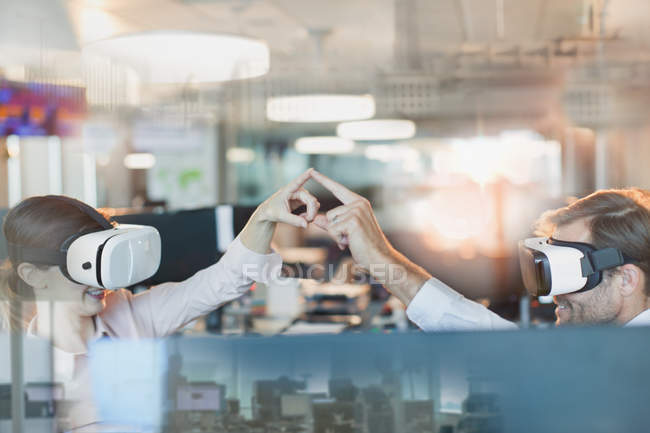 Computer programmers using virtual reality simulator glasses, touching fingers in office — Stock Photo