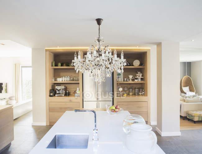 Chandelier hanging over luxury kitchen island — Stock Photo