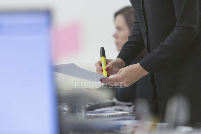 Businesswoman highlighting paperwork in office — Stock Photo