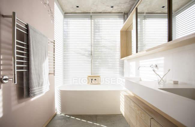 Luz brillando a través de persianas detrás de bañera en baño de lujo - foto de stock