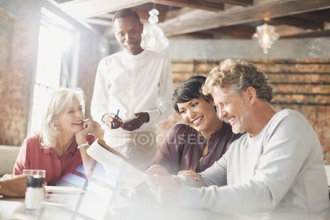 Teniendo orden en la mesa de restaurante camarero - foto de stock