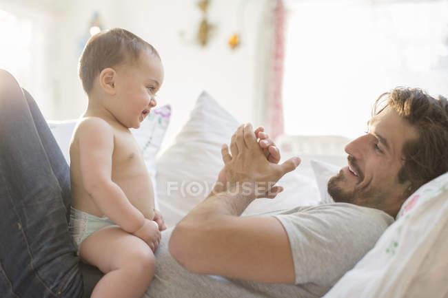 Веселий батька, грати з сином дитини на дивані — стокове фото