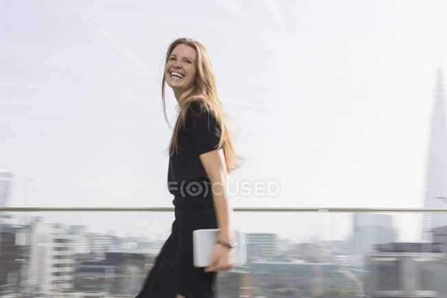 Portrait laughing businesswoman with digital tablet on urban balcony — Stock Photo