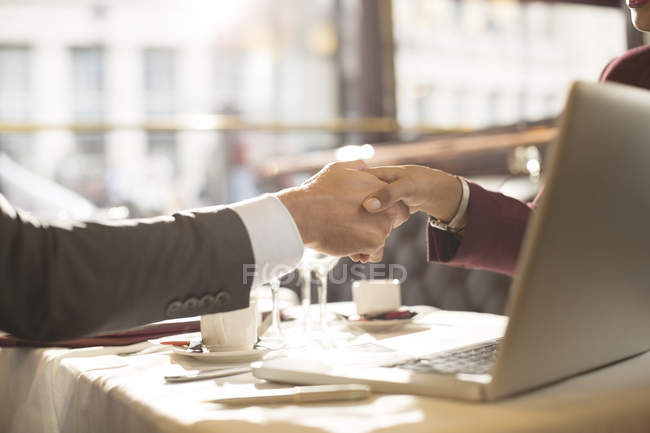 Cropped image of business people shaking hands in restaurant — Stock Photo