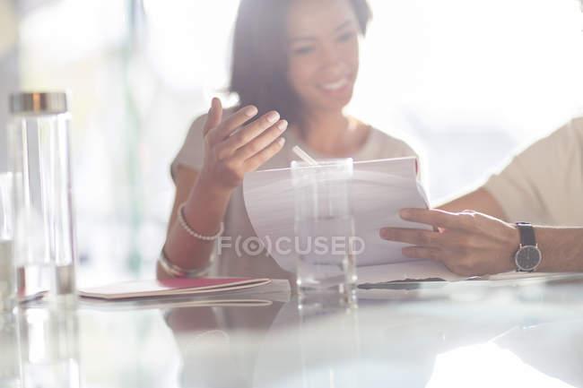 Businesswoman gesturing to paperwork in meeting — Stock Photo