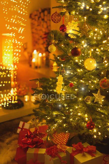 Closeup of gifts under illuminated Christmas tree — Stock Photo