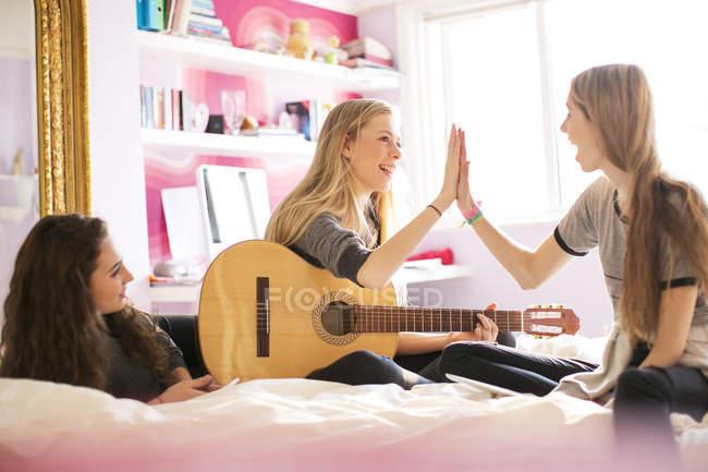 Ragazze adolescenti con il fiving alto chitarra sul letto — Foto stock