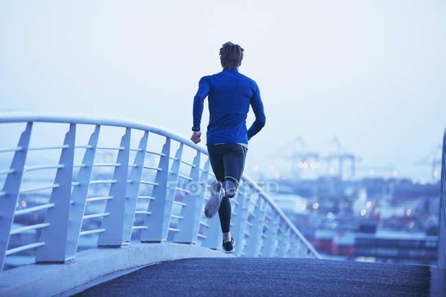Мужчина бегает по городскому пешеходному мосту на рассвете — стоковое фото