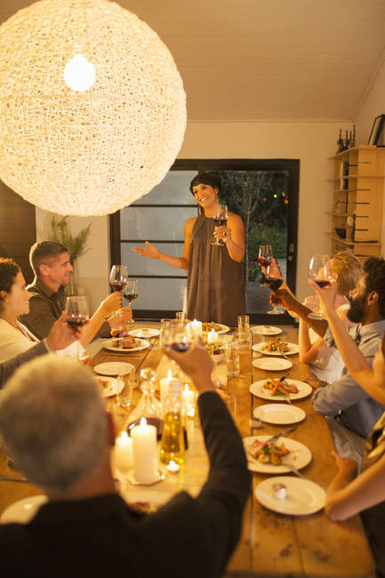 Woman giving toast at dinner party — Stock Photo