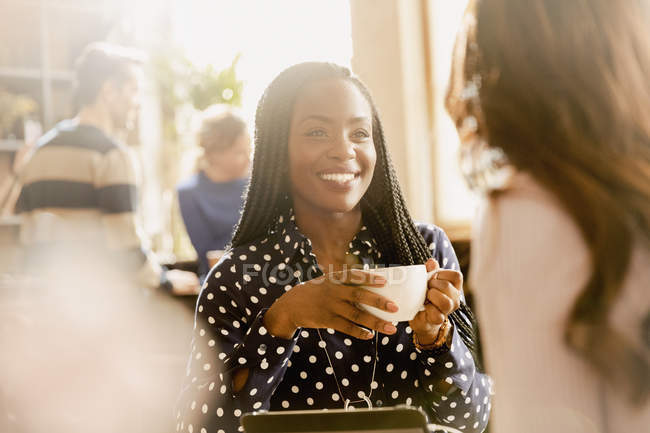 Smiling women friends drinking coffee and talking in cafe — Stock Photo