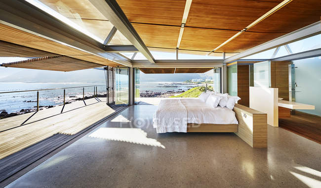 Modern luxury home showcase bed open to patio with sunny ocean view — Stock Photo