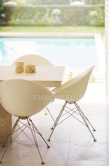 Sillas alrededor de la mesa junto a la piscina - foto de stock