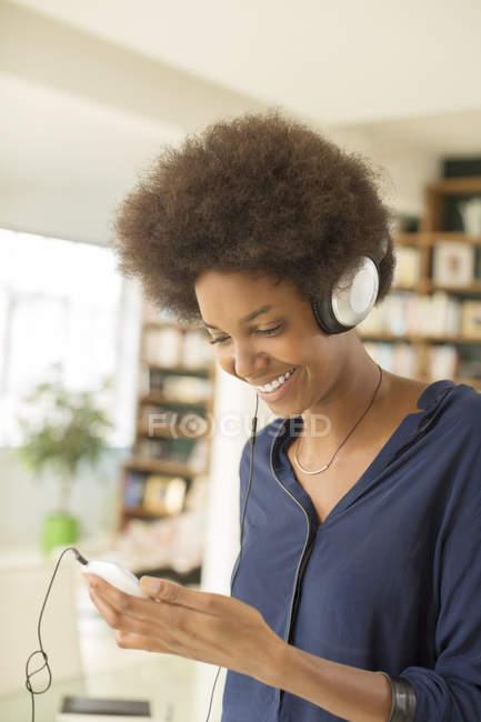Жінка, слухаючи навушники у вітальні на дому — стокове фото