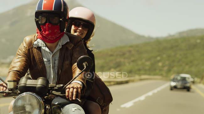 Jovem casal de equitação da motocicleta na estrada ensolarada — Fotografia de Stock