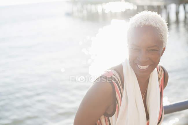 Retrato de sonriente negro mujer en frente al mar - foto de stock